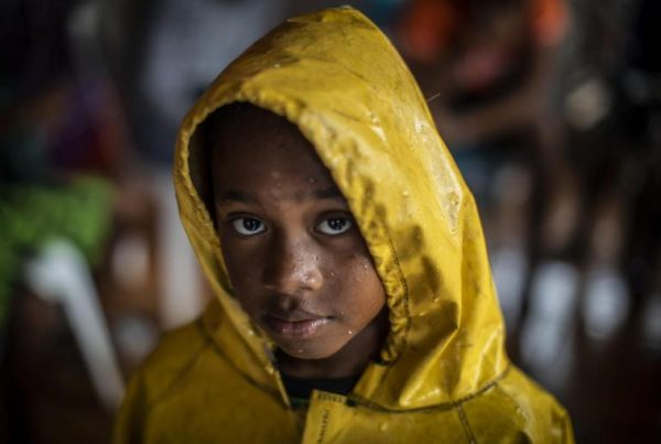 UNICEF/UN0372373/Ocon/AFP-Services A girl protects herself from the heavy rains by wearing a raincoat as she returns home from a shelter after the passage of Hurricane Iota in Nicaragua, in Bilwi, on November 16, 2020.